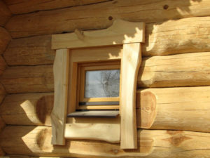 Красивое деревянное окно в бане с оригинальным наличником